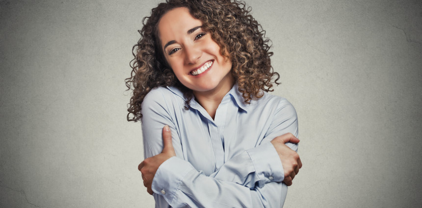 Closeup portrait confident smiling woman holding hugging herself isolated grey wall background. Positive human emotion, facial expression, feeling, reaction, situation, attitude. Love yourself concept