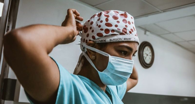 Medical professional putting a face mask on
